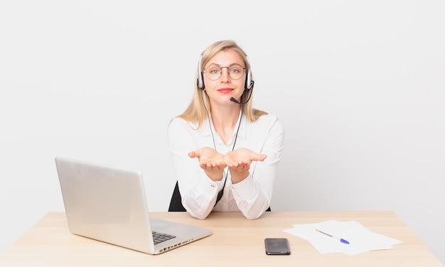 Blondynka ładna młoda blond kobieta uśmiecha się radośnie z przyjaznym i oferuje i pokazuje koncepcję oraz pracuje z laptopem