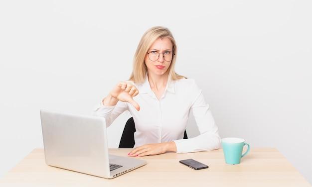 Blondynka ładna młoda blondynka czuje się krzyż, pokazując kciuk w dół i pracując z laptopem