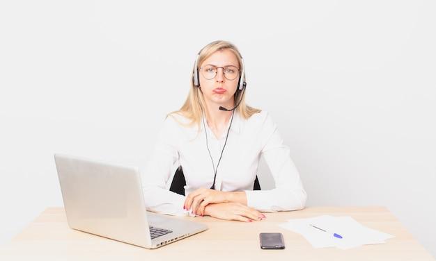 Blondynka ładna młoda blondynka czuje się smutna i jęczy z nieszczęśliwym spojrzeniem, płacze i pracuje z laptopem