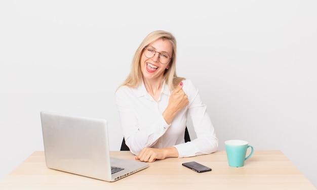 Blondynka ładna młoda blondynka czuje się szczęśliwa i stoi przed wyzwaniem lub świętuje i pracuje z laptopem