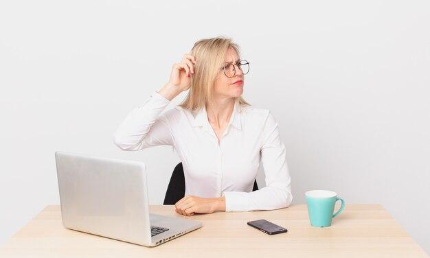 Blondynka ładna młoda blondynka czuje się zakłopotana i zdezorientowana, drapiąc się po głowie i pracując z laptopem