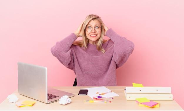 Blondynka ładna młoda blondynka czuje się zestresowana, niespokojna lub przestraszona, z rękami na głowie i pracuje z laptopem