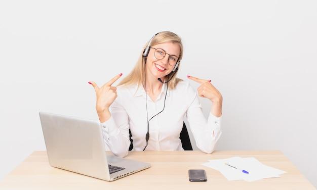 Blondynka ładna młoda blondynka uśmiecha się pewnie wskazując na swój szeroki uśmiech i pracuje z laptopem