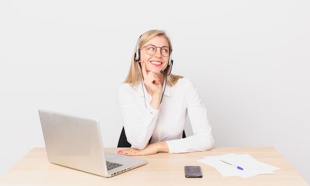 Blondynka ładna młoda blondynka uśmiecha się ze szczęśliwym, pewnym siebie wyrazem twarzy z ręką na brodzie i pracuje z laptopem