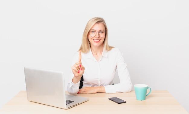 Blondynka ładna młoda blondynka uśmiechnięta i wyglądająca przyjaźnie, pokazująca numer jeden i pracująca z laptopem