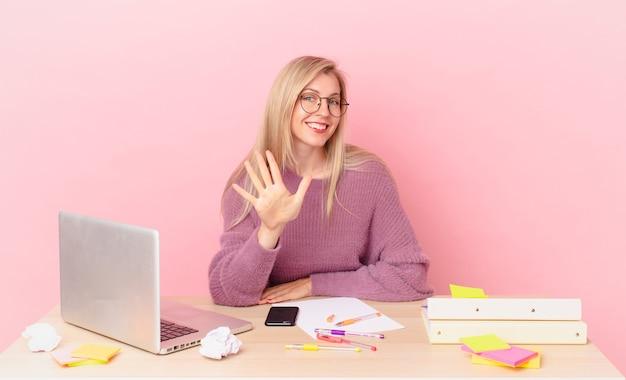Blondynka ładna młoda blondynka uśmiechnięta i wyglądająca przyjaźnie, pokazująca numer pięć i pracująca z laptopem