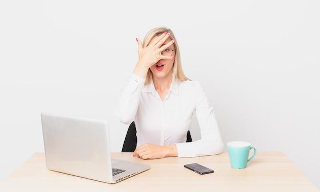 Blondynka ładna młoda blondynka wygląda na zszokowaną, przestraszoną lub przerażoną, zakrywa twarz dłonią i pracuje z laptopem