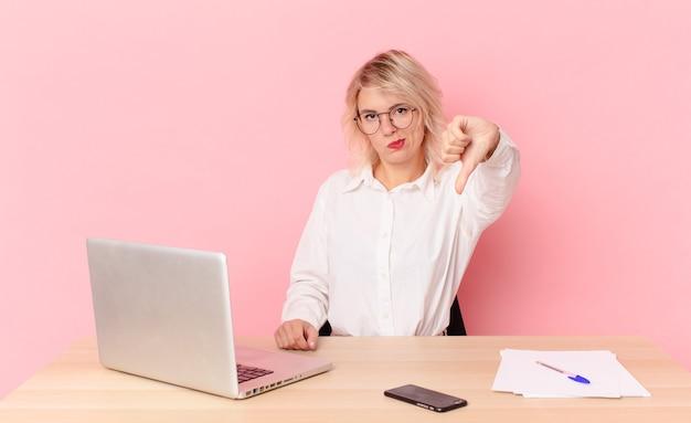 Blondynka ładna młoda kobieta ładna uczucie krzyż, pokazując kciuk w dół. koncepcja biurka w miejscu pracy