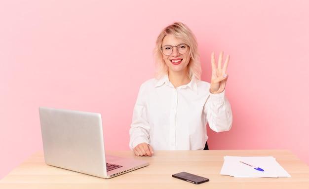 Blondynka ładna młoda kobieta ładna uśmiechnięta i patrząc przyjazna, pokazując numer trzy. koncepcja biurka w miejscu pracy