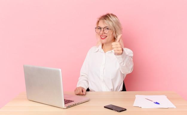 Blondynka ładna młoda ładna kobieta czuje się dumna, uśmiechając się pozytywnie z kciukami do góry. koncepcja biurka w miejscu pracy