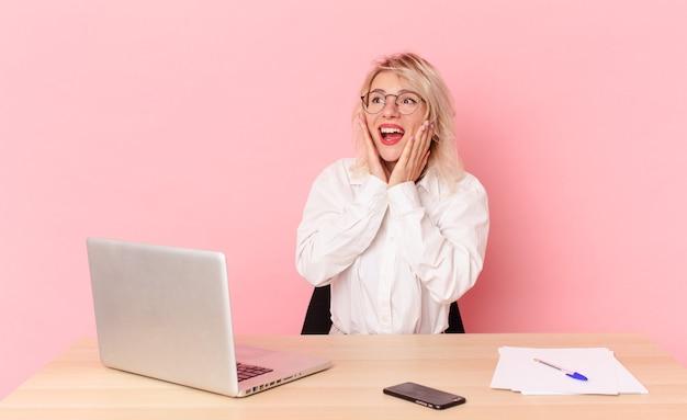 Blondynka ładna młoda ładna kobieta czuje się szczęśliwa, podekscytowana i zdziwiona. koncepcja biurka w miejscu pracy