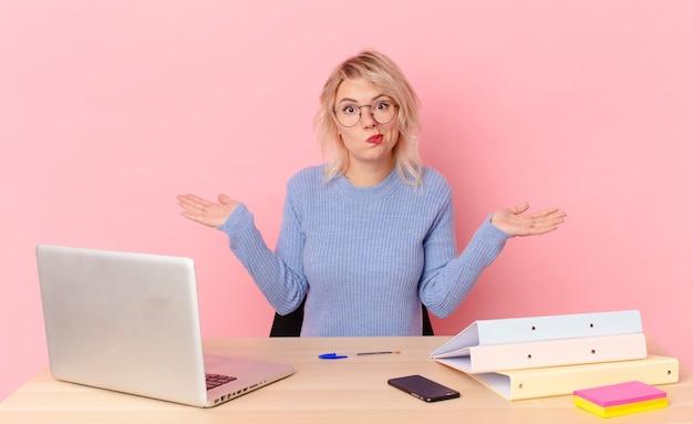 Blondynka ładna młoda ładna kobieta czuje się zdziwiona i zdezorientowana i wątpi koncepcja biurka w miejscu pracy