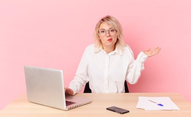 Blondynka ładna młoda ładna kobieta czuje się zdziwiona i zdezorientowana i wątpi. koncepcja biurka w miejscu pracy