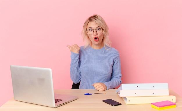 Blondynka ładna młoda ładna kobieta patrząc zdumiona z niedowierzaniem. koncepcja biurka w miejscu pracy