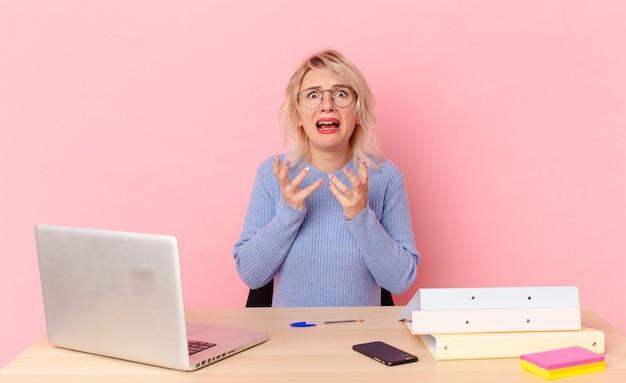 Blondynka ładna młoda ładna kobieta szuka zdesperowany, sfrustrowany i zestresowany. koncepcja biurka w miejscu pracy