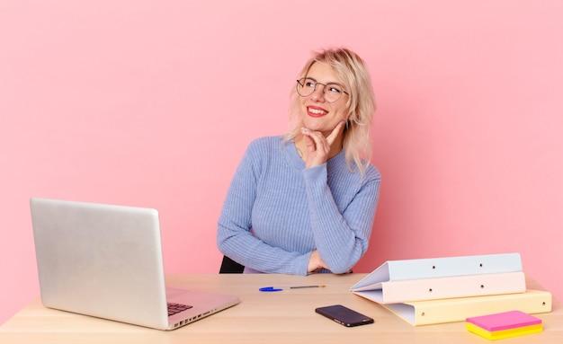 Blondynka ładna młoda ładna kobieta uśmiecha się szczęśliwie i marzeń lub wątpi. koncepcja biurka w miejscu pracy