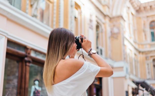 Blondynka ładny fotograf kobieta z aparatem retro w dłoniach podczas robienia zdjęć w miejskiej architekturze starej. odkryj nowe miejsca. widok z tyłu