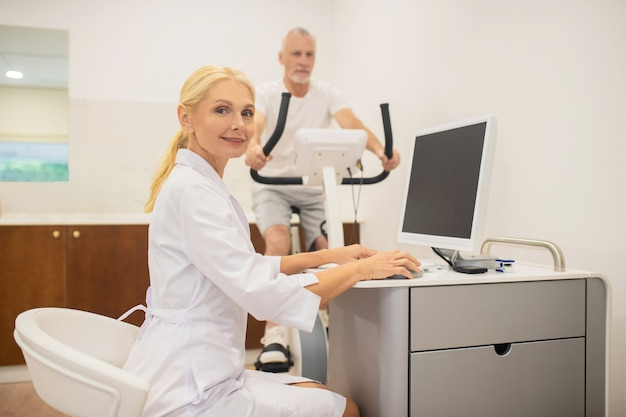 Blondynka lekarz siedzi przy laptopie, podczas gdy jej pacjent ćwiczenia na bieżni