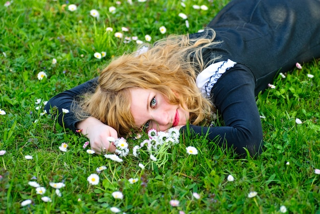 Blondynka leży na trawie i trzyma kwiat do girlandy od stokrotek, portret na zewnątrz.