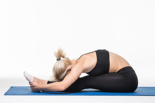 Blondynka ma czas na relaks jogi po ćwiczeniach sportowych na podłodze, siedząc na mapie sportowej