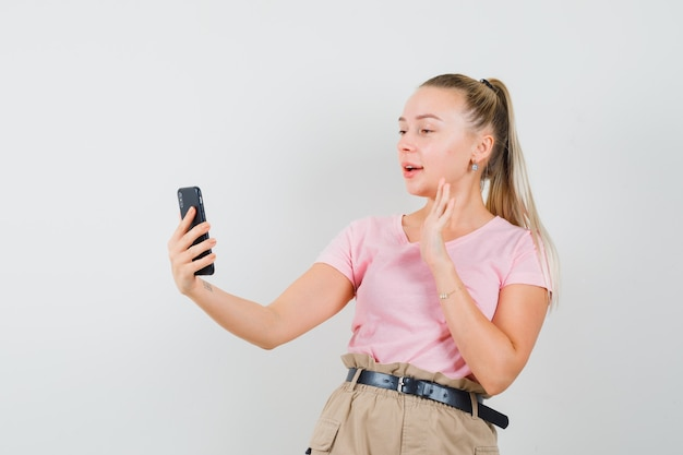 Blondynka macha ręką na czacie wideo w t-shirt, spodnie i patrząc jowialnie, widok z przodu.