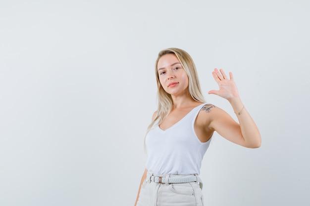 Blondynka macha ręką, żeby się pożegnać w podkoszulku, spodniach i wyglądająca na pewną siebie