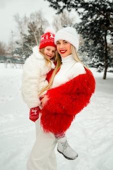 Blondynka mama w jasnych ubraniach trzyma córkę w ramionach przed zimowym krajobrazem. wygląd rodziny.