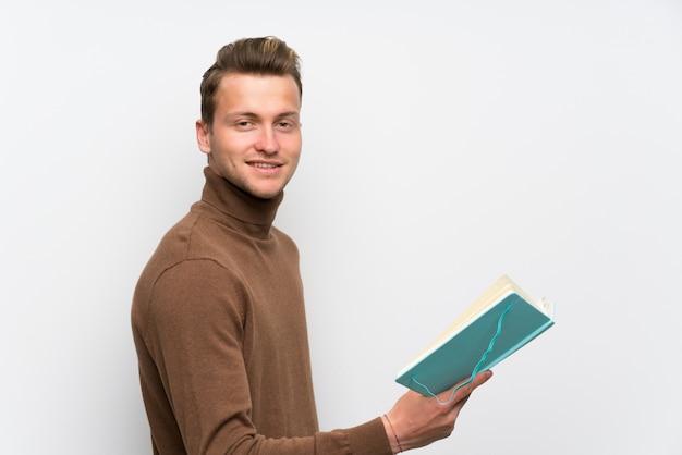 Blondynka mężczyzna nad odosobnioną biel ścianą trzyma książkę i cieszy się czytać