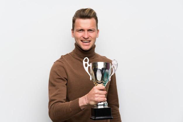 Blondynka mężczyzna nad odosobnioną biel ścianą trzyma trofeum