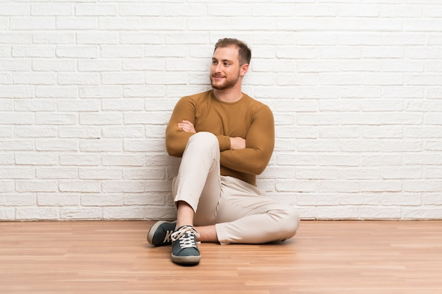 Blondynka mężczyzna siedzi na podłodze, patrząc z boku