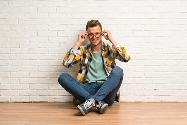 Blondynka mężczyzna siedzi na podłodze w okularach i zaskoczony