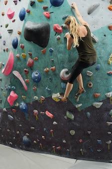 Blondynka młoda aktywna kobieta trzyma sztuczne skały na ścianie podczas wspinaczki w siłowni lub centrum sportów ekstremalnych