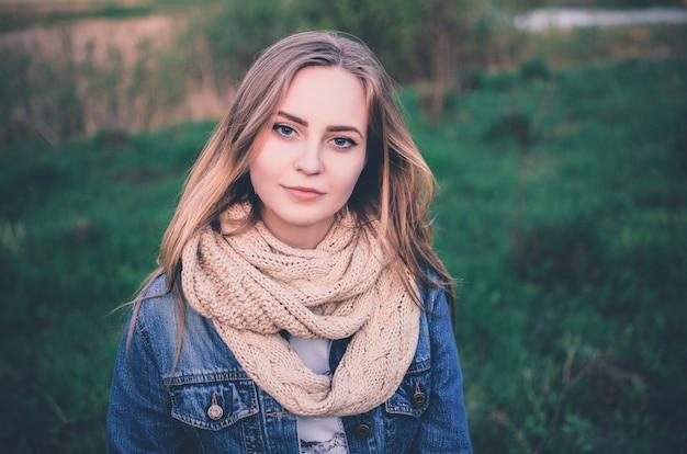 Blondynka młoda europejska kobieta w niebieskim kolorze denim i szalik na zewnątrz. naturalny makijaż. trawa zielona natura na tle.