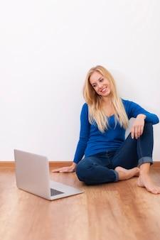 Blondynka młoda kobieta siedzi na drewnianej podłodze z laptopem