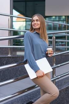 Blondynka młoda kobieta uśmiecha portret trzymając laptop i kawę, na sobie niebieską delikatną koszulę na tle nowoczesnego budynku