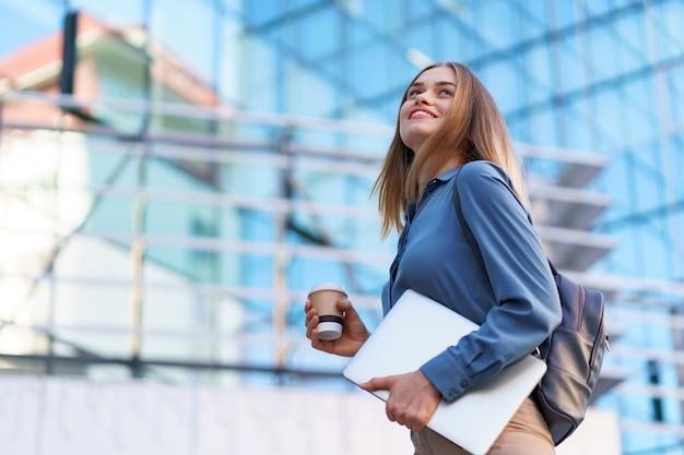 Blondynka młoda kobieta uśmiecha się portret trzymając laptop i kawę, na sobie niebieską delikatną koszulę na nowoczesnym budynku