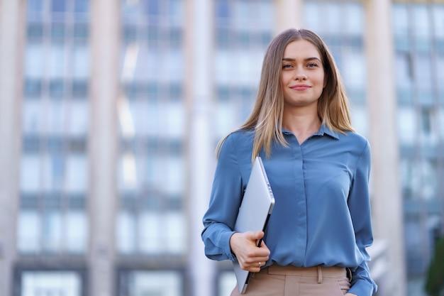 Blondynka młoda kobieta uśmiechnięty portret na sobie niebieską delikatną koszulę na budynku
