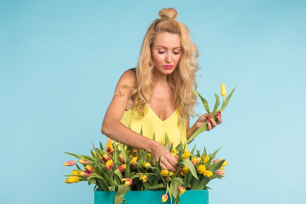 Blondynka młoda kobieta z bukietem tulipanów na niebieskiej ścianie