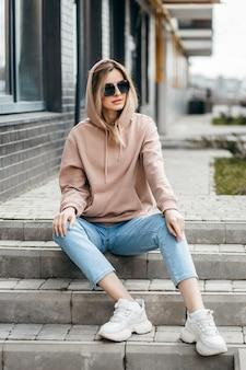 Blondynka moda w brązowej bluzie oversize z kapturem, okularach i dżinsach, pozowanie, siedząc na schodach