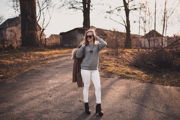 Blondynka modelka w białe spodnie, okulary przeciwsłoneczne, brązowy płaszcz