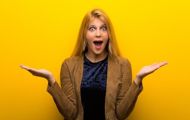 Blondynka na żywe żółte tło z niespodzianką i zszokowany wyraz twarzy