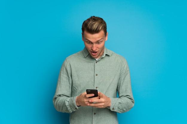 Blondynka nad odosobnioną błękit ścianą zaskakującą i wysyłającą wiadomość