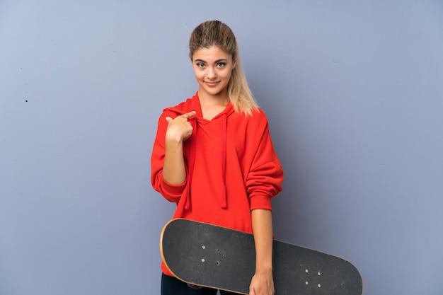 Blondynka nastolatka łyżwiarz dziewczyna na szarej ścianie z zaskoczenia wyraz twarzy