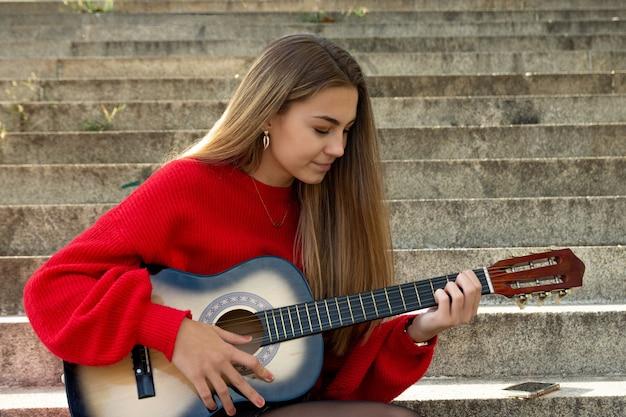 Blondynka nastolatka ubrana w czerwony sweter gra na gitarze.