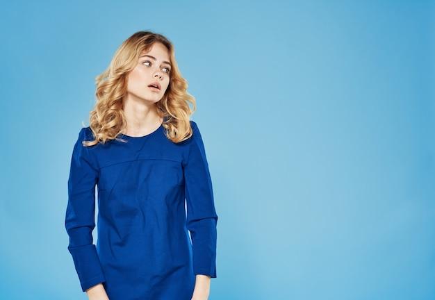 Blondynka, niebieska sukienka, emocje, styl życia, studio, niebieskie tło. wysokiej jakości zdjęcie