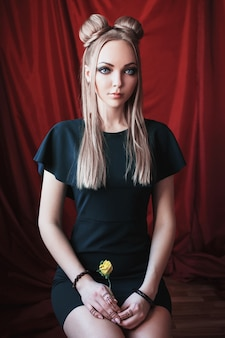 Blondynka o dużych niebieskich oczach jak elf, długie białe włosy w kok, dziewczyna z fryzurą i makijażem w zielonej sukience na czerwonym