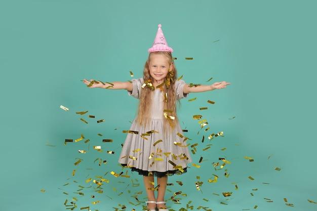 Blondynka o niebieskich oczach w szarej sukience w kapeluszu wszystkiego najlepszego z okazji urodzin łapie konfetti