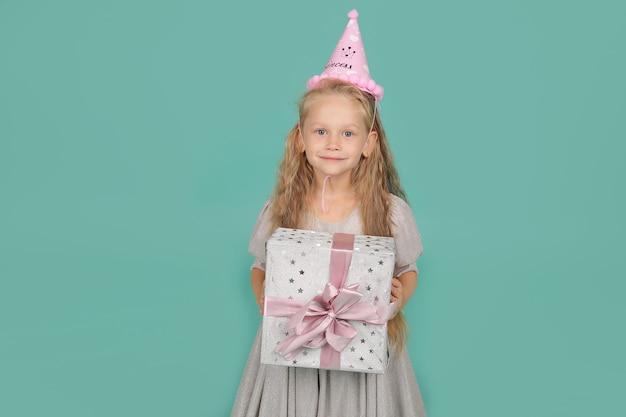 Blondynka o niebieskich oczach w szarej sukience w kapeluszu z okazji urodzin pudełko na prezent
