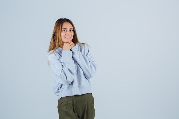 Blondynka opierając podbródek na dłoniach, ściskając ręce w oliwkowo-niebieskiej bluzie i spodniach i patrząc na szczęśliwą. przedni widok.