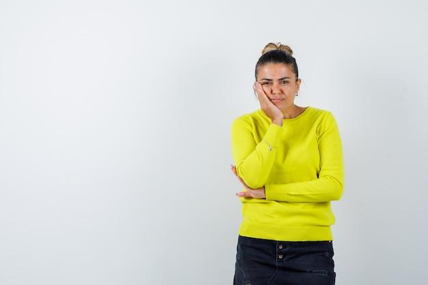 Blondynka opierając policzek na dłoni, trzymając dłoń na łokciu w żółtym swetrze i czarnych spodniach i patrząc zamyślona